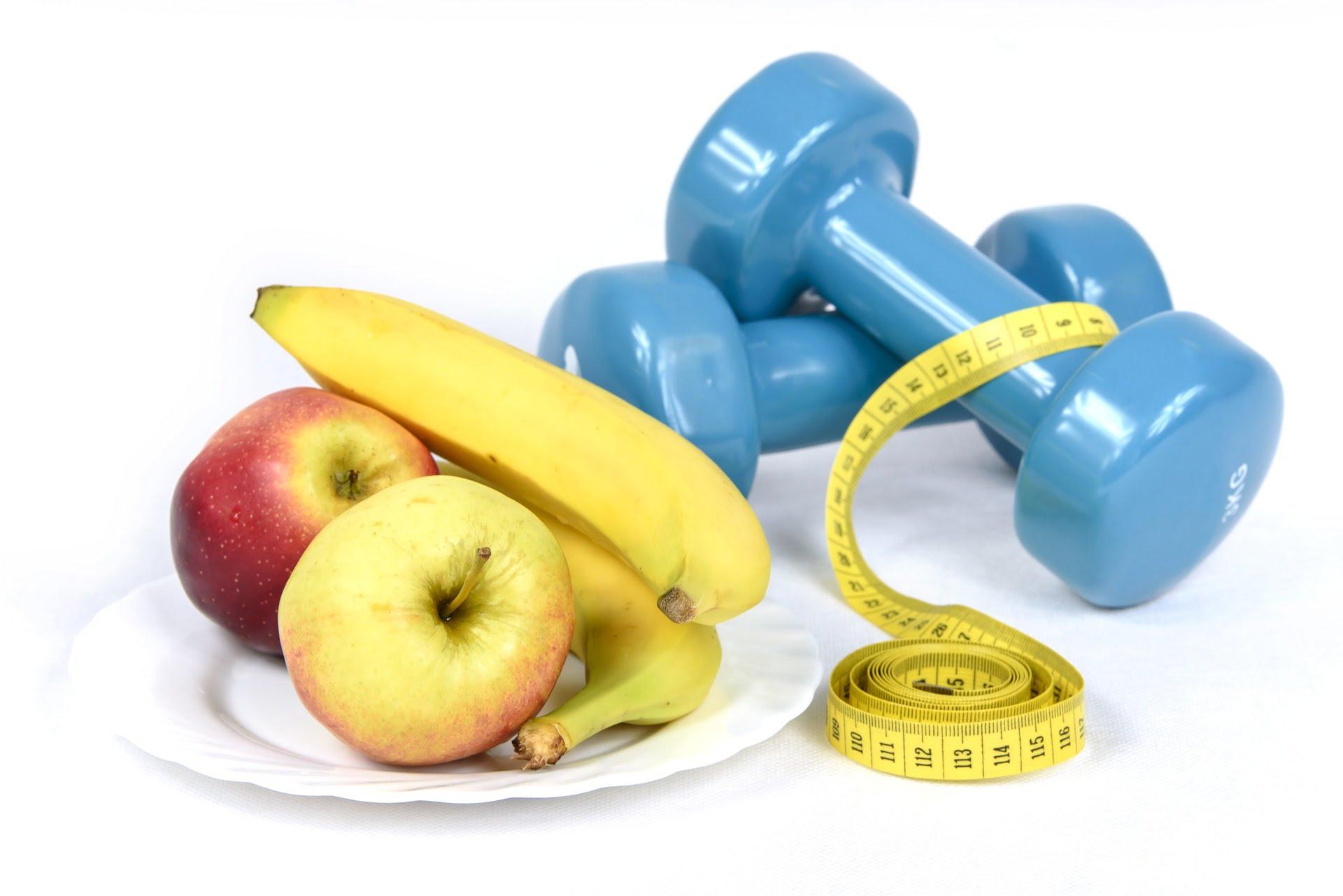 Talerz z jabłkami i bananami, obok dwie niebieskie hantle i centymetr krawiecki