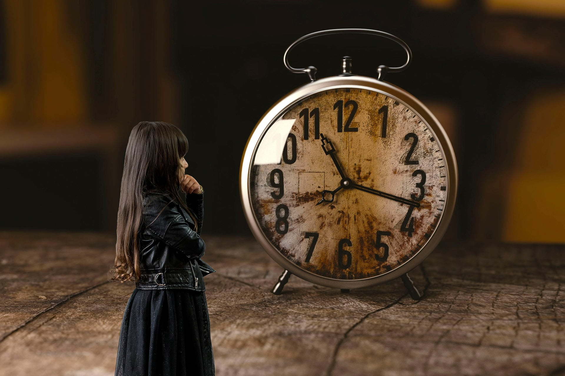 Dziewczynka, która patrzy na budzik i zastanawia się, która jest godzina