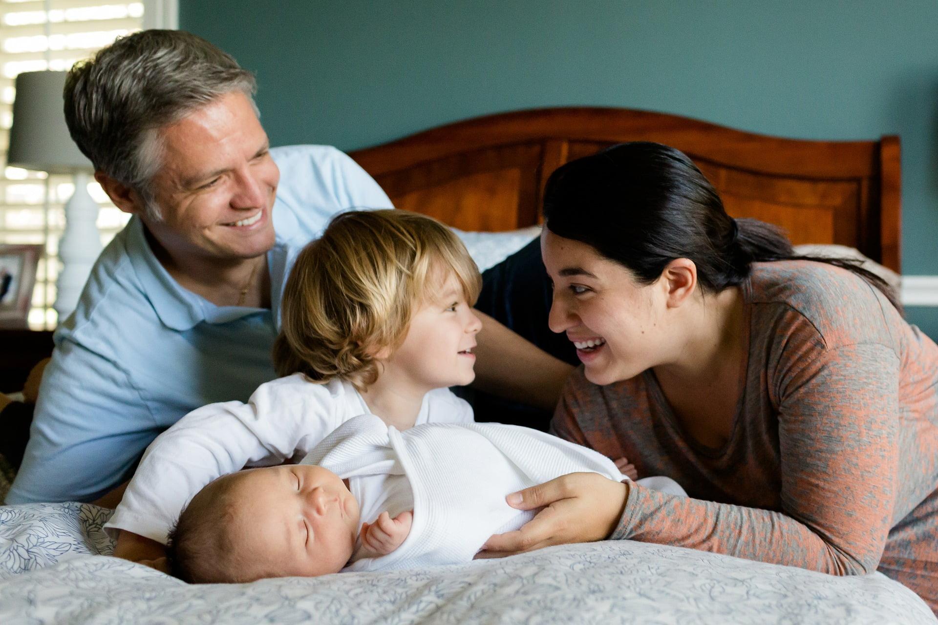 Rodzina leży na łóżku, dwójka małych dzieci i rodzice