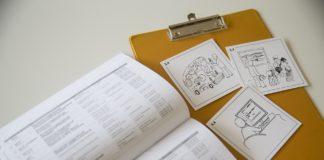 Na stole leżą otwarta książka i żółta podkładka, a na niej 3 białe karteczki z rysunkami