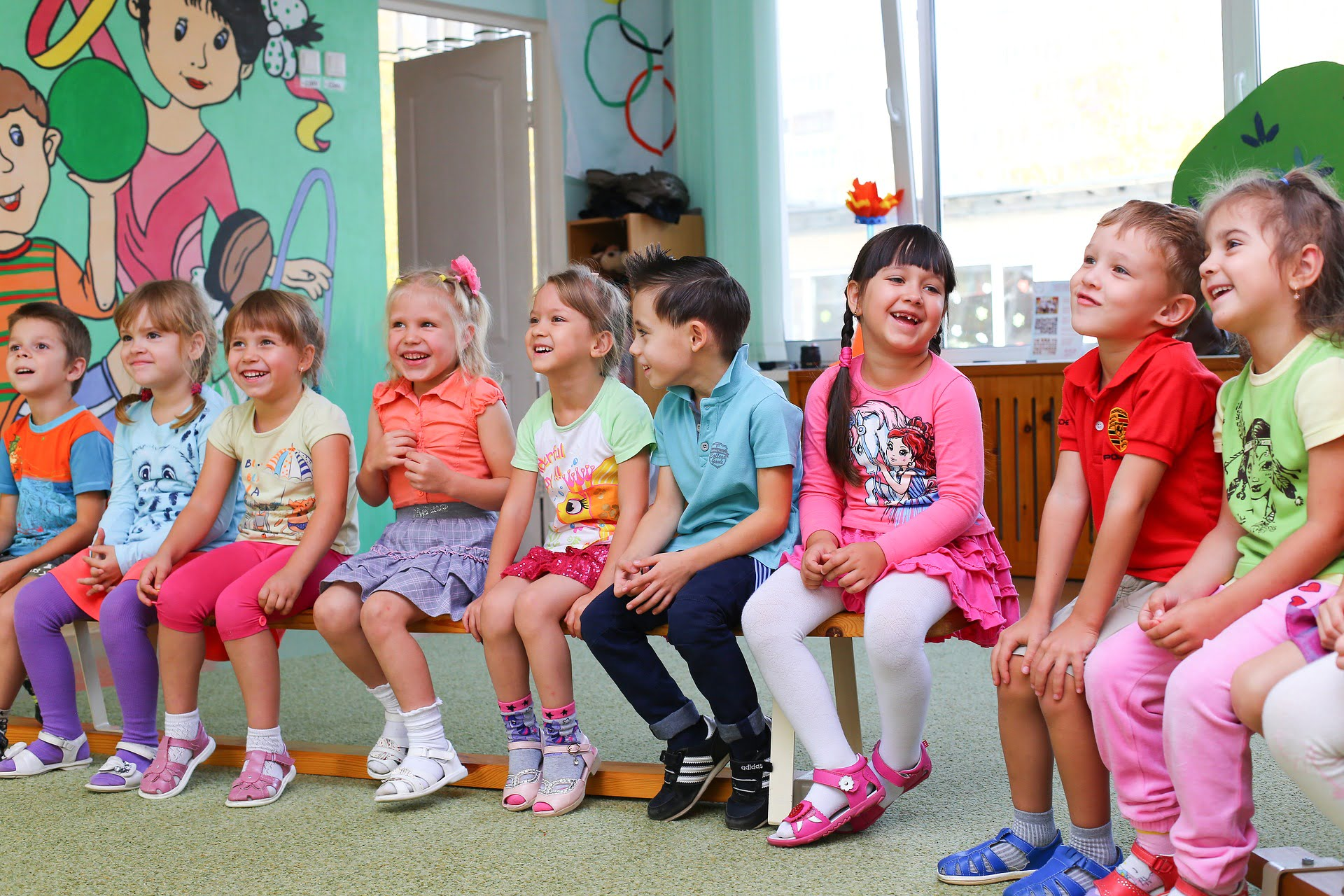 Grupa dzieci siedzi na ławce, wszyscy się śmieją