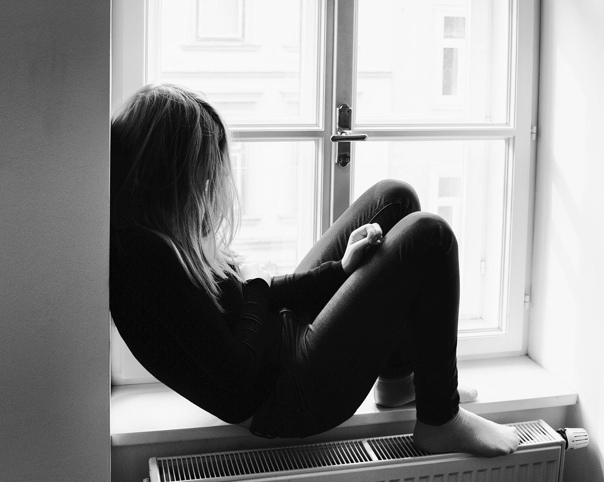 Biało-czarne zdjęcie, na którym smutna dziewczyna siedzi na parapecie