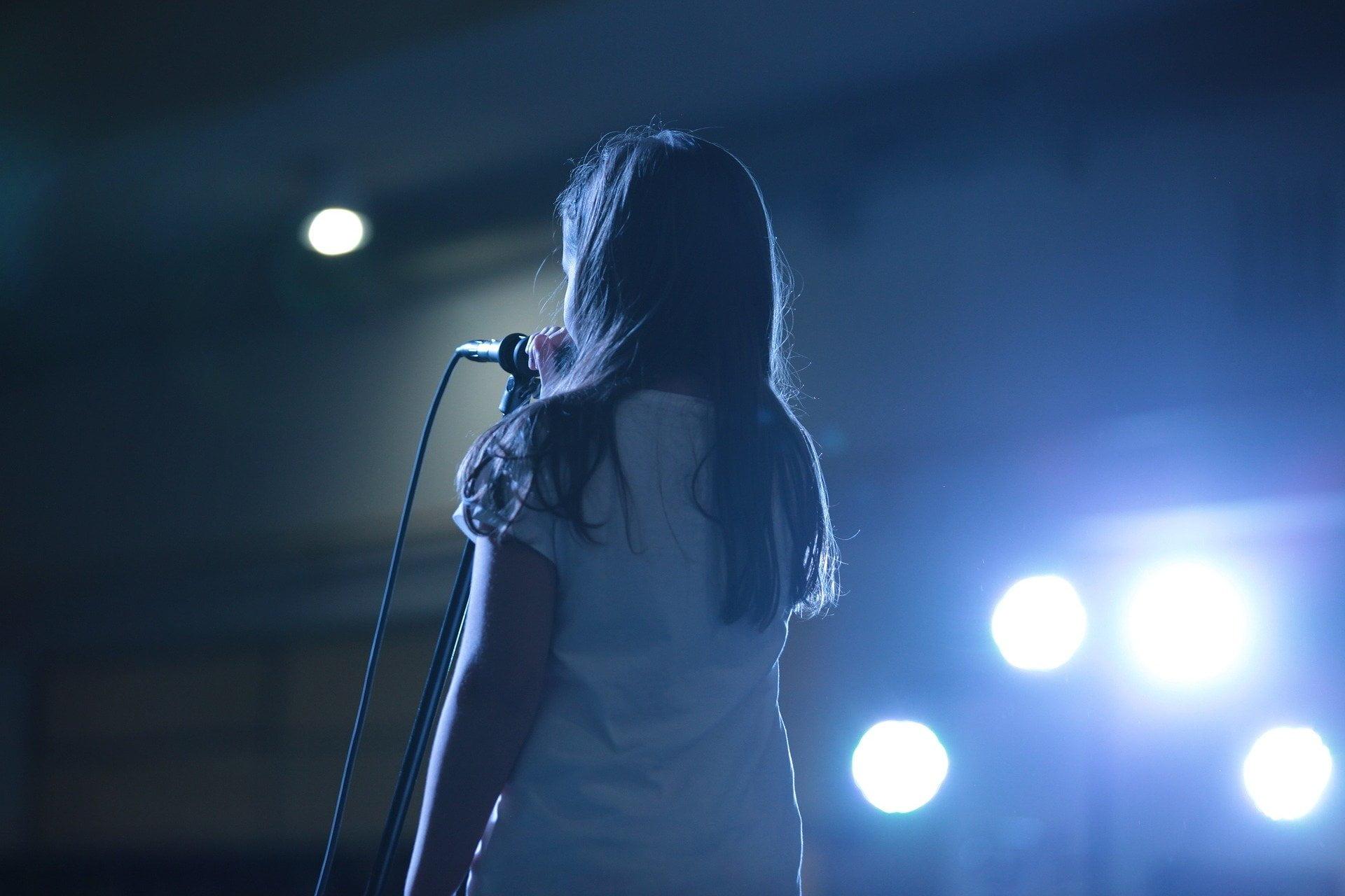 Dziewczynka odwrócona tyłem, przed sobą ma mikrofon