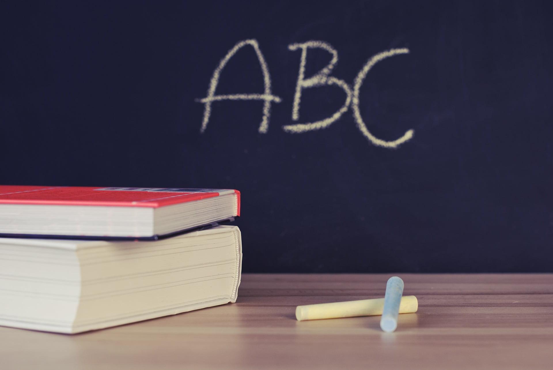 Na biurku leżą dwie książki, obok nich żółta i niebieska kreda, w tle tablica, na której napisane jest ABC